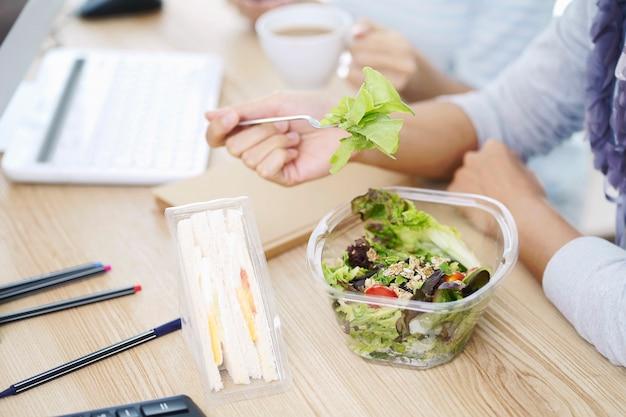 샐러드 상자와 계란 샌드위치 상자를 먹는 비즈니스 여성. 직장에서 파트너십과 함께 일하기 위해 점심을 먹습니다.