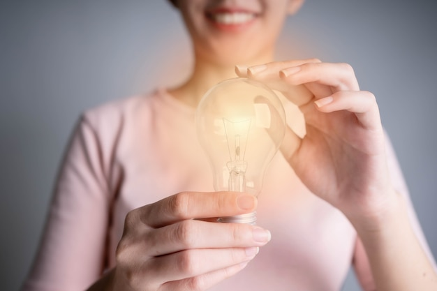 Business women hand holding light bulb, concept of new ideas with innovation and creativity