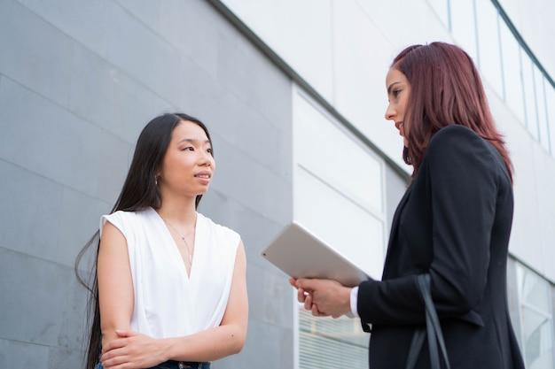 専門家会議を行うビジネスウーマンアジア人と白人女性労働者が話をする