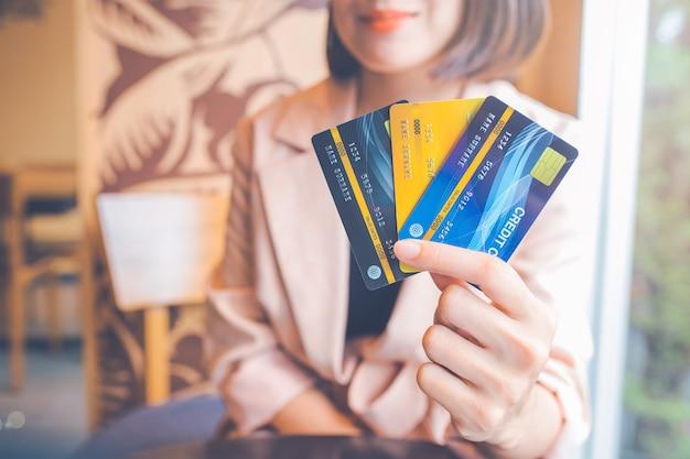 ビジネスウーマンは3枚のクレジットカードを持っています。