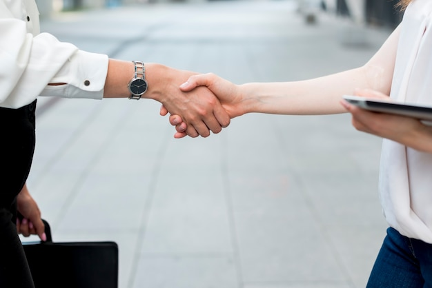 Business women holding hands in the street