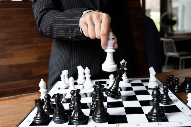 Business women holding king chess on board challenges planning business strategy to success concept