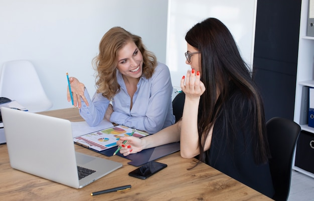 Business women at office desk working together on laptop, teamwork concept