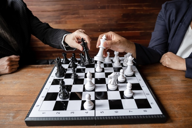 Business women play chess on board challenges planning business strategy to success concept
