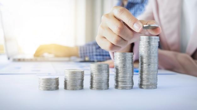 비즈니스 여성 돈 성장 개념에 대 한 동전 스택 돈을 넣어 미래를위한 돈을 저축.