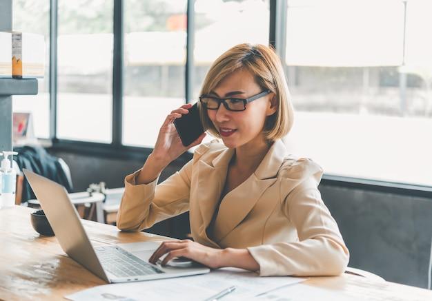 Деловые женщины сидят по телефону во время работы на ноутбуке и проверяют документы бизнес-графика, работают в финансовой сфере