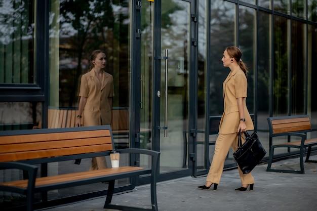 비즈니스 여성 스타일. 일 하 러가 서류 가방을 가진 여자입니다. 세련 된 사무실 옷에 아름 다운 미소 여성의 초상화. 높은 해상도.