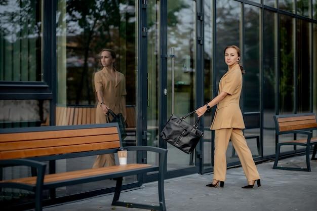 ビジネスウーマンスタイル。仕事に行くブリーフケースを持つ女性。スタイリッシュなオフィス服で美しい笑顔の女性の肖像画。高解像度。