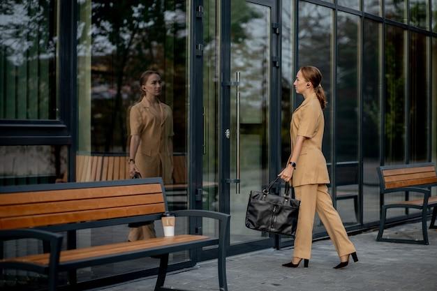 Стиль деловых женщин. женщина с портфелем идет на работу. портрет красивой улыбающейся девушки в стильной офисной одежде
