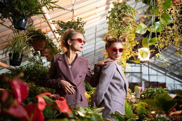Бизнес-леди. стильные привлекательные женщины, стоящие со своим коллегой, положив руку ей на плечо