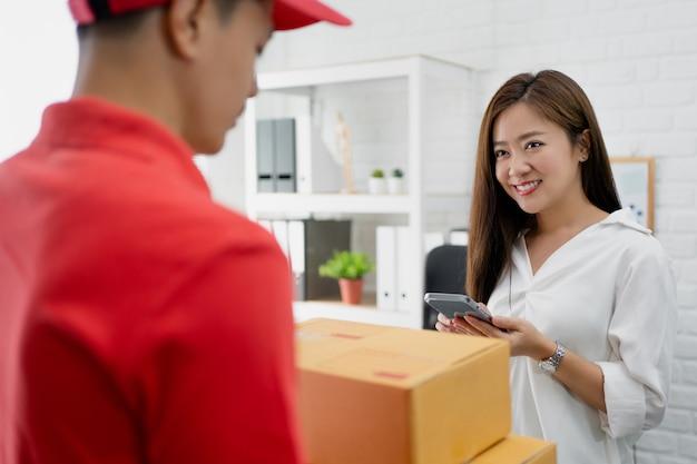 ビジネスウーマンは宅配から箱を受け取ります。彼女はオフィスにいます