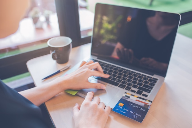 Business women use credit cards and laptop computers to shop online.
