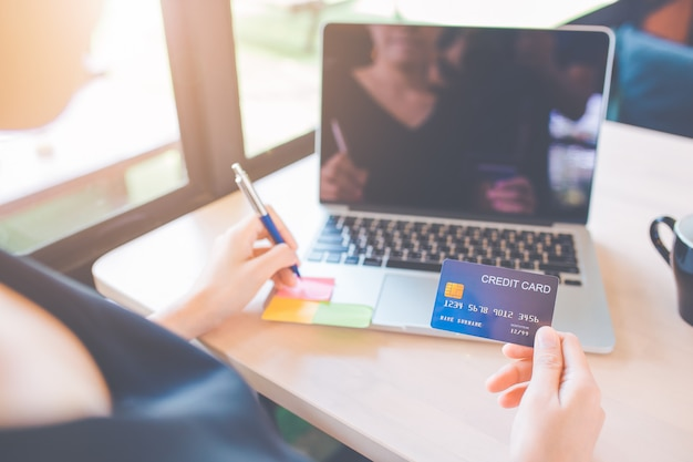 Business women use credit cards to shop online.