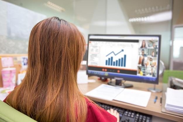 Деловые женщины смотрят графики с экрана портативного компьютера для онлайн-встреч.