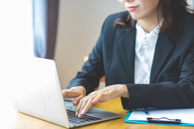 공식적인 옷을 입고 비즈니스 여성 집에서 일하는 아이디어에 노트북에 문서를 입력하고 있습니다.