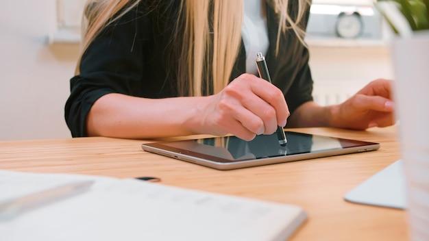 Деловые женщины, работающие над планшетом в офисе, привлекательная белокурая женщина с длинными волосами в элегантном костюме, сидящая за деревянным столом с компьютером и сосредоточенная на работе над планшетом с ручкой в светлом офисе