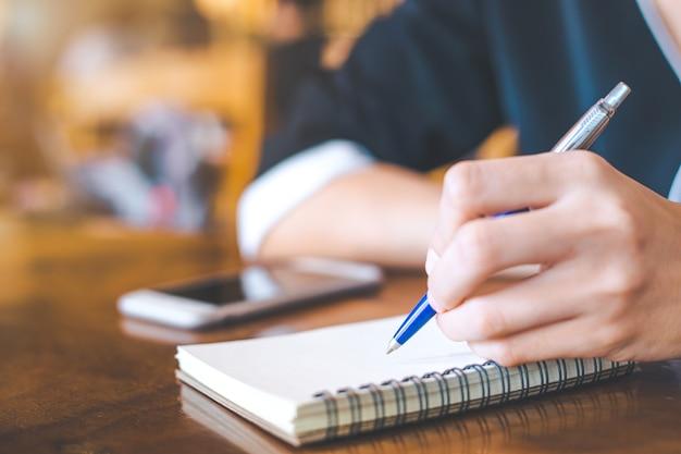 Business women writing on a notebook