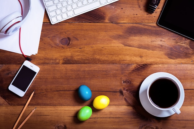 Business work desk and happy easter holiday multicolored eggs background