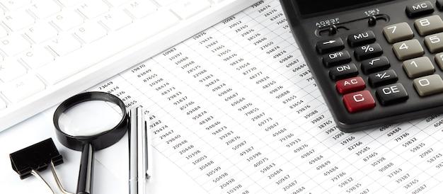 흰색 사무실 책상 평면도에 차트, 계산기, 돋보기 및 키보드로 비즈니스 작업