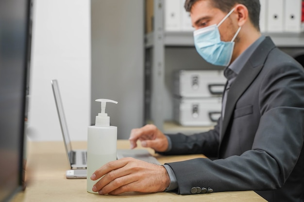 Business worker with face mask back at work in office after lockdown using sanitizer gel