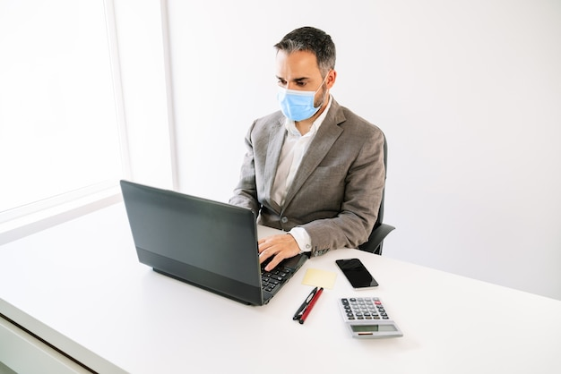 Covid19 코로나 바이러스 전염병으로 인해 계산기, 휴대 전화, 포스트잇, 흰색 백라이트 및 작업 공간이 모두있는 펜으로 얼굴 마스크가있는 노트북에서 작업하는 비즈니스 작업자