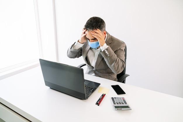 노트북, 계산기, 휴대 전화, 게시, 펜으로 covid19 코로나 바이러스 전염병으로 인해 얼굴 마스크로 매우 걱정되는 그의 머리에 손을 대고 일하는 비즈니스 작업자