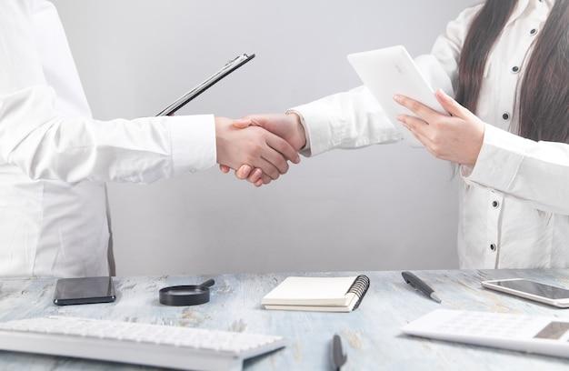 Деловые работники, пожимая руки в офисе.