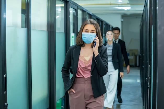 コロナウイルスまたはcovid-19発生後のパンデミック後の新しい正常な変化の間に、ビジネスオフィスの社会的距離ポリシーに従って働いている医療用顔面マスクを着用しているビジネスワーカー。
