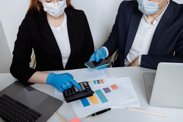 Business workers working at office wearing protective mask and gloves