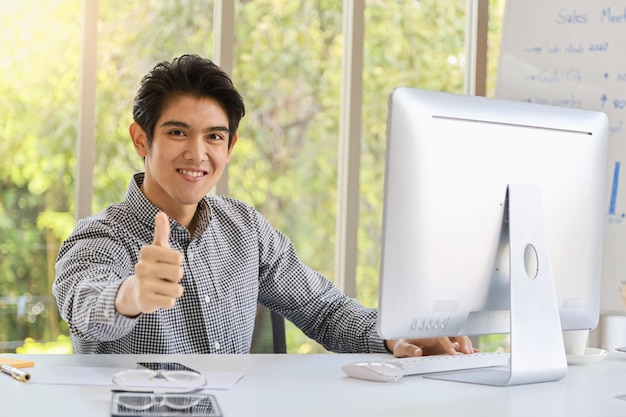 Business and workplace concept. portrait of smart young asian businessman sitting in the office and smile and show thump up with computer, mobile phone, document,, reading glasses and pen.