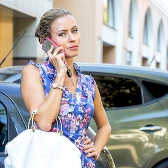 차 근처에서 전화 통화 하는 비즈니스 젊은 아름 다운 소녀