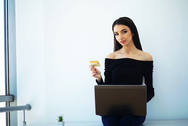 Business. young business woman holding credit card in hands. sits on the table at the big light office and works on the computer. work at home. high resolution