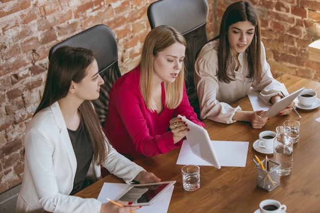 チームと近代的なオフィスにビジネスの若い白人女性
