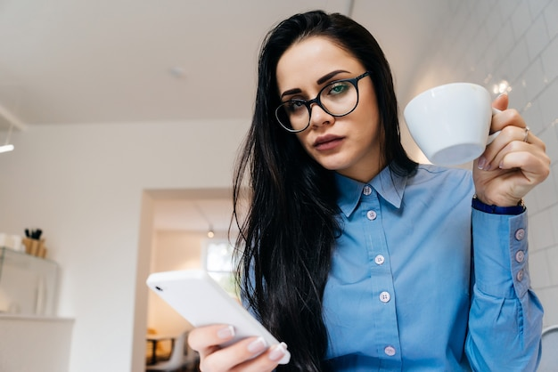Business young girl freelancer in a blue shirt and glasses breakfast in a cafe, drinking coffee