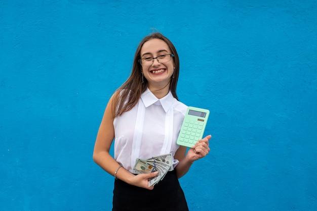 파란색 배경에 고립 된 녹색 계산기와 비즈니스 젊은 아가씨. 금융 개념