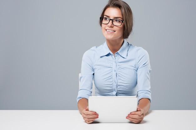 Giovane donna di affari che per mezzo della compressa digitale