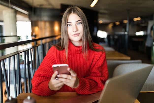 Деловая молодая женщина с ноутбуком и телефоном в кафе