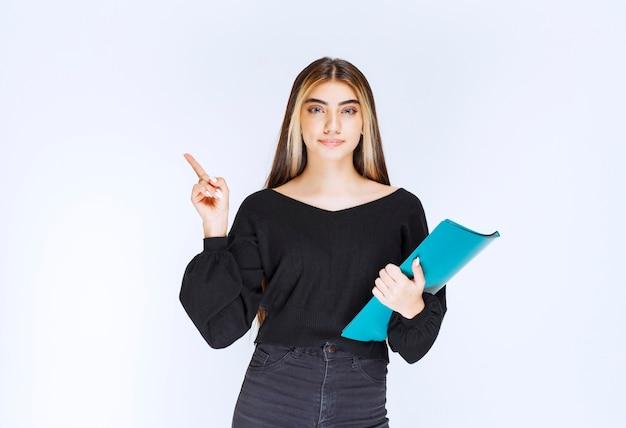 Businesslady держит синюю папку и указывая на своего коллегу. фото высокого качества