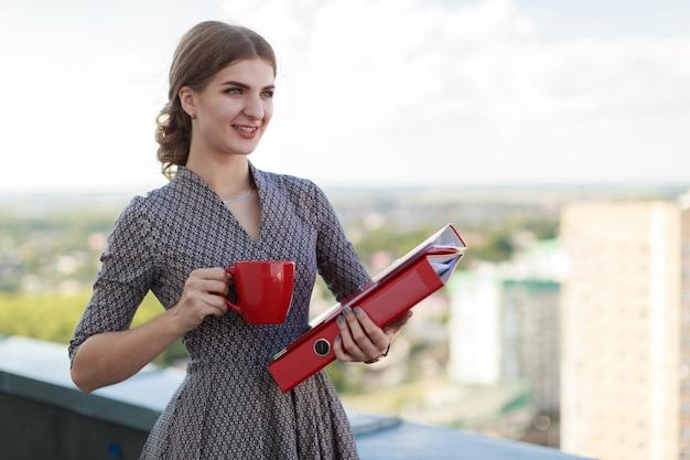 パターン化されたドレスの魅力的なbusinessladyは屋根の上に立ち、紙フォルダーと赤カップを保持