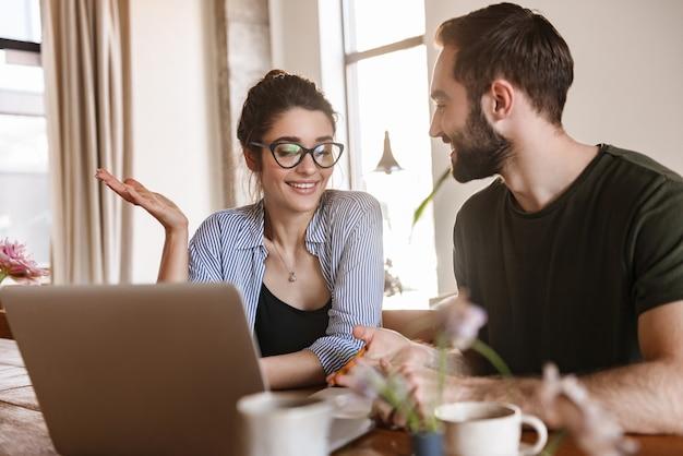 Деловая брюнетка пара мужчина и женщина пьют кофе и вместе работают над ноутбуком, сидя за столом у себя дома