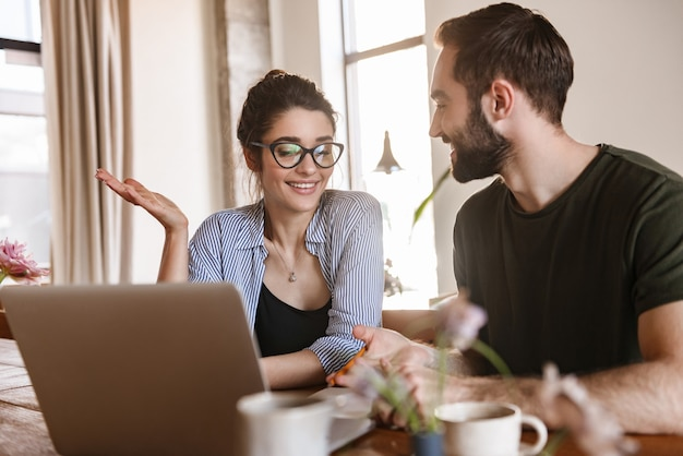 Businesslike brunette couple man and woman drinking coffee and working on laptop together while sitting at table at home