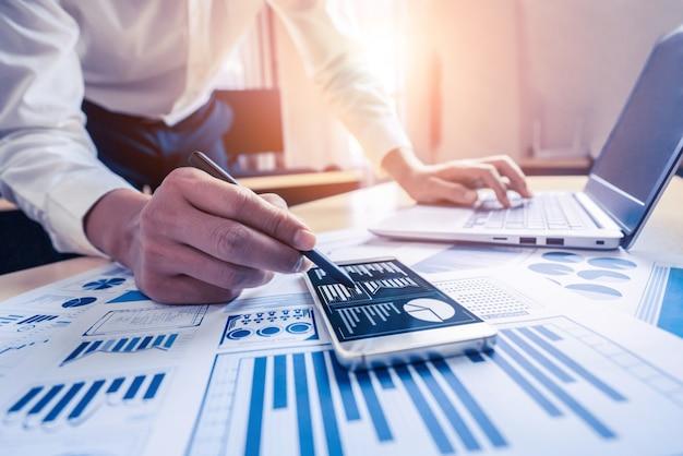 Бухгалтер бизнесмена или финансовый эксперт анализируют график бизнес-отчета и финансовую диаграмму в корпоративном офисе. понятие экономики финансов, банковского дела и исследования фондового рынка.