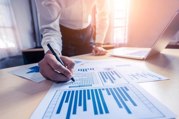 ビジネスマンの会計士または財務の専門家は、企業のオフィスでビジネスレポートのグラフと財務チャートを分析します。金融経済、銀行業、株式市場調査の概念。