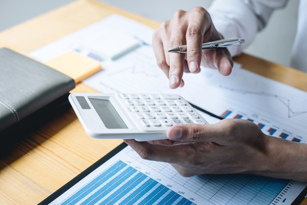 Businessman accountant working analyzing and calculating expense financial annual financial report balance sheet statement and analyze document graph and diagram, doing finance making notes on report