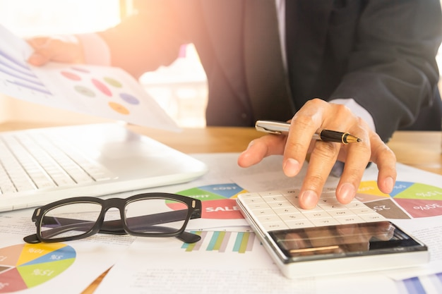 Businessman or accountant working on calculator to calculate business data concept at office.