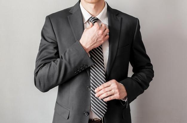 Бизнесмен, поправляя галстук, на сером фоне, бизнес-концепция