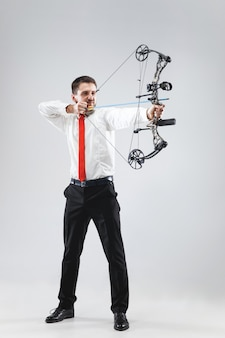 灰色のスタジオの背景に分離された弓と矢でターゲットを狙うビジネスマン。ビジネス、目標、挑戦、競争、達成の概念