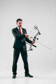 灰色のスタジオの背景に分離された弓と矢でターゲットを狙うビジネスマン。ビジネス、目標、挑戦、競争、達成、目的、勝利、勝利、明快さ、勝者と成功の概念