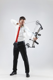 灰色のスタジオの背景に分離された弓と矢でターゲットを狙うビジネスマン。 無料写真