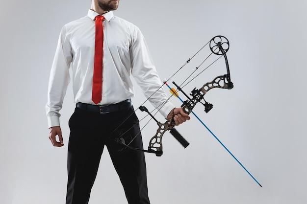 Бизнесмен, направленный в цель с луком и стрелами, изолированный на серой стене студии
